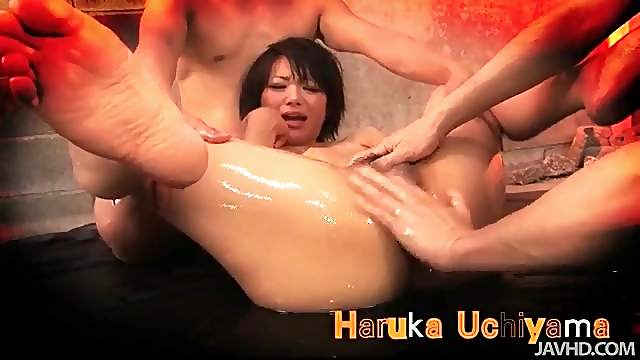 Sensually pouring oil over her Japanese body