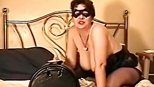 Mature woman in a mask toys herself and rides a Sybian saddle