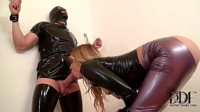 Chained man blown by a beauty in latex