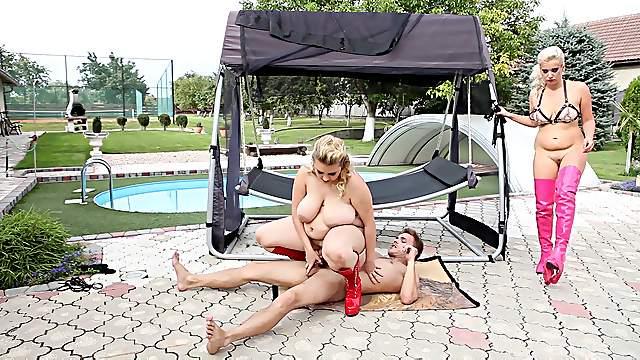 Curvy females share a man in dirty outdoor femdom